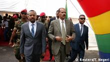 Ethopia's president Abiy Ahmed and Eritrea's president, wearings suits and surrounded by security and soldiers, walk at the inauguration ceremony on Monday