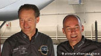 Bertrand Picard and Andre Borschberg in the hanger, the tail of the plane in the background
