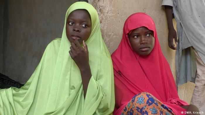 Two young girls, sisters Aisha and Falmata, wearing a green and red hijab respectively, sit by a wall