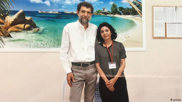 Osman Kavala visited by his wife, Ayse Bugra, in prison. A big picture of the Mediterranean is in the background.