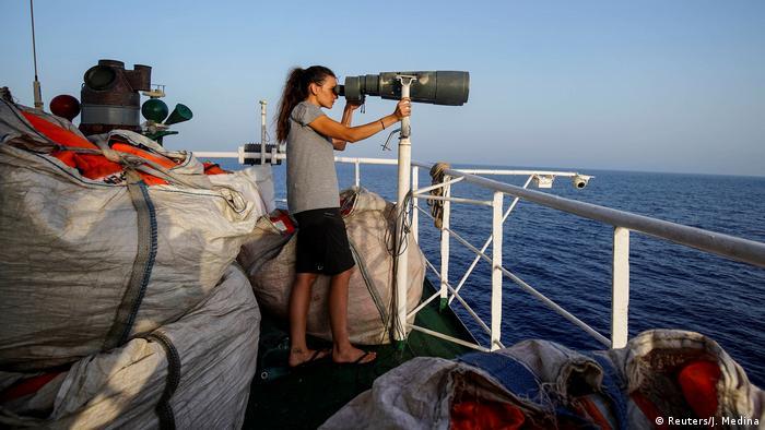 Спасатель из организации Proactiva Open Arms с биноклем в поисках людей в открытом море