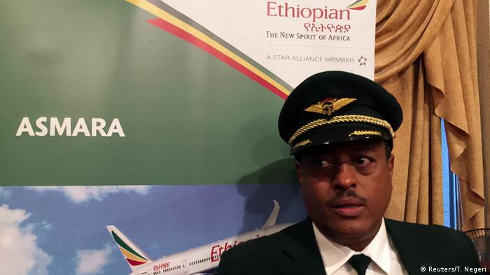 Pilot Yoseph Hailu standing next to an Ethiopian Airlines poster with its logo The New Spirit of Africa and the destination of his flight – Asmara