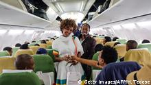 A woman in a white dress and scarf is standing in the aisle of a passenger plane with a glass in her hand, chatting to two men. (Getty Images/AFP/H. Tedese)