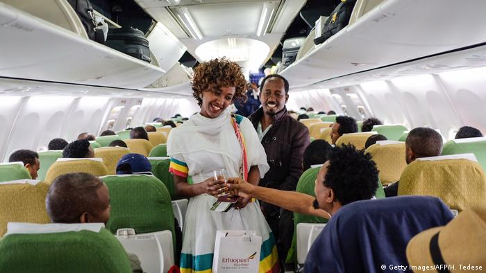 A woman in a white dress and scarf is standing in the aisle of a passenger plane with a glass in her hand, chatting to two men.