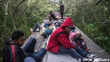 Migrants stand and sit on top of the so-called Beast, the freight train that travels across Mexico, from Guatemala to the US border