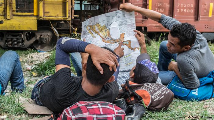 Migrants rest on the ground and examine a map while waiting for La Bestia