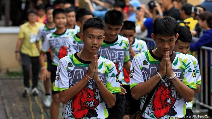 Meninos tailandeses fazem tradicional saudação tailandesa após receberem alta de hospital