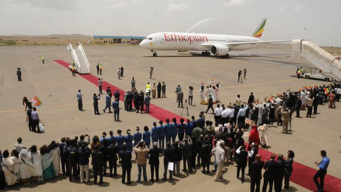 A crowd of people line the tarmac at Asmara International Airport as an Ethiopian Airlines Boeing 787 taxis down the runway