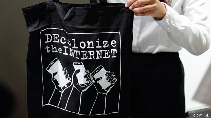 A person holds up a black t-shirt emblazoned with the words 'decolonise the internet' and an image of three hands holding smartphones
