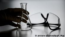 A person holds a beaker next to a pair of protective glasses (picture-alliance/dpa/F. May)