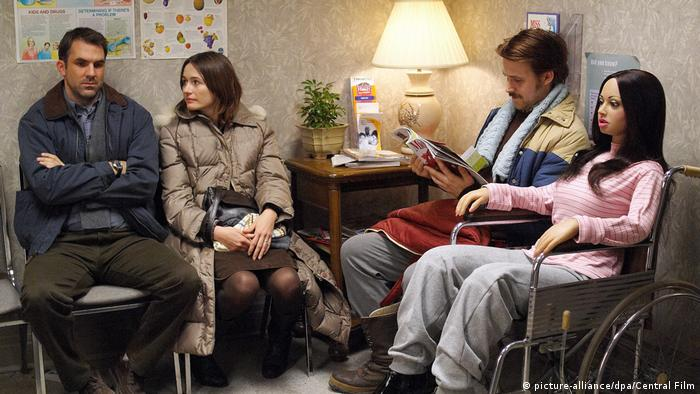 two men, a woman and a doll sitting inn a waiting room (picture-alliance/dpa/Central Film)