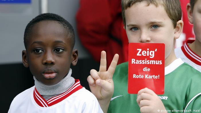 Надпись на плакате: Покажи расизму красную карточку!