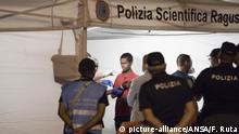 Police check a migrant disembarked from Frontex ship Protector at the port of Pozzallo, Sicily