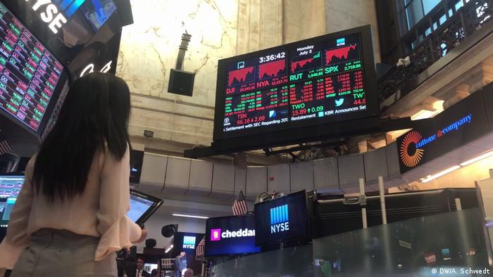 Lauren Simmons looks up at the price board on the New York Stock Exchange