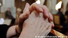 ARCHIV - Eine alte Frau hat die Hände zum Gebet gefaltet während eines Gottesdienstes, aufgenommen am 25.03.2007. (Zu dpa «Buß- und Bettag» vom 22.11.2017). Foto: Arno Burgi/dpa-Zentralbild/dpa +++(c) dpa - Bildfunk+++ | Verwendung weltweit