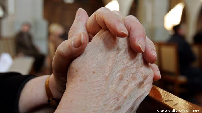 Starija žena moli u crkvi