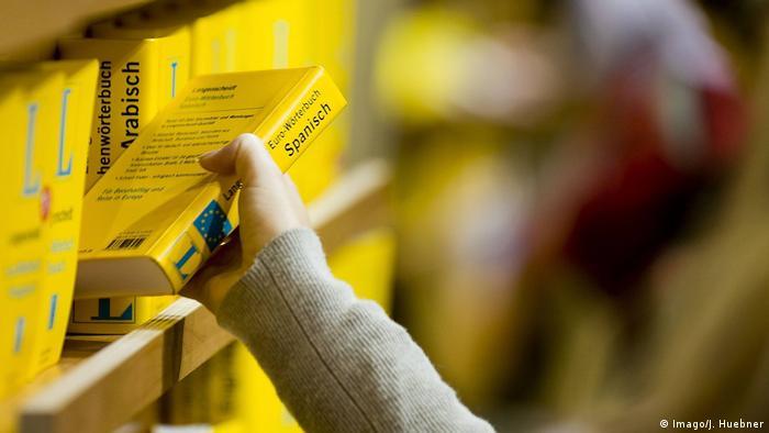 hand grabbing dictionary off the shelf   Spanisch (Imago/J. Huebner)