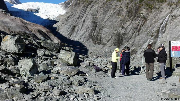Группа туристов стоит у подножия горы