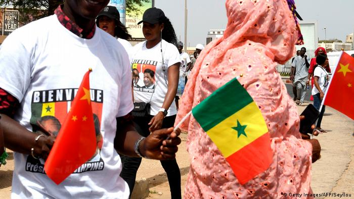 A man in a printed white t-shirt holding the Chinese and Senegalese flags stands next to a woman in a pink headscarf holding a Chinese flag to welcome China's President Xi Jinping to Dakar. (Getty Images/AFP/Seyllou)