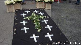 Weiße Holzkreuze auf einem schwarzen Tuch in der Wuppertaler Fußgängerzone (Foto: akzeptierende-eltern.de)