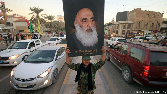 A person in Basra, Iraq, holds up a poster of influential cleric Ayatollah Ali al-Sistani (Getty Images/AFP/H.M. Ali)
