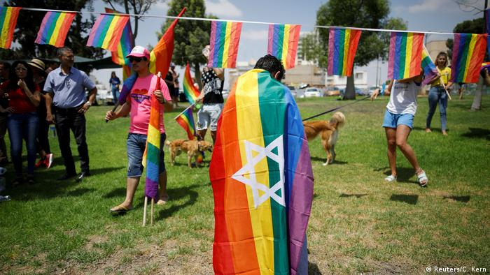 An Israeli protester in Beersheba is draped in a rainbow flag with a Star of David on it.