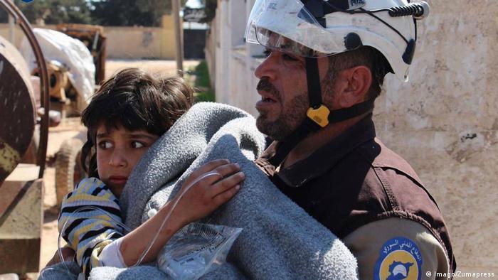 Волонтер Белых касок со спасенным ребенком на руках