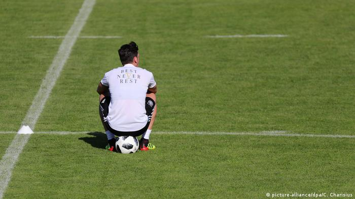 Mesut Özil sits on a ball during a training session (picture-alliance dpa 6be0c4839