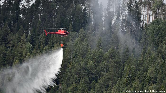 Firefighters try to put out a fire in Sweden with a helicopter