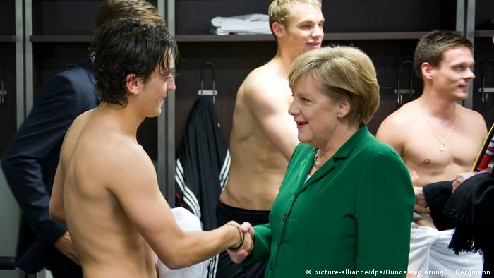Mesut Özil meets Angela Merkel in a football changing room in 2010 (picture-alliance/dpa/Bundesregierung/G. Bergmann)