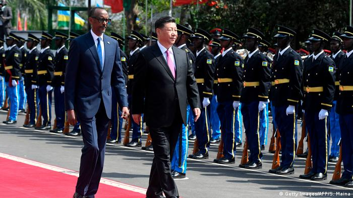 Rwanda's President Kagame and Chinese President Xi walking along a red carpet lined by Rwandan soldiers