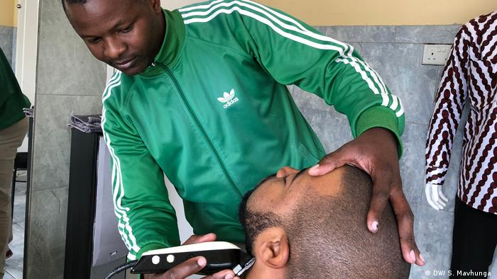 Barber Collins Chigwagwa uses an electric razer to shave a customer's chin