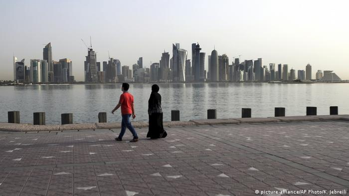 Two people walk in front of a wide view of the Doha skyline (picture-alliance/AP Photo/K. Jebreili)