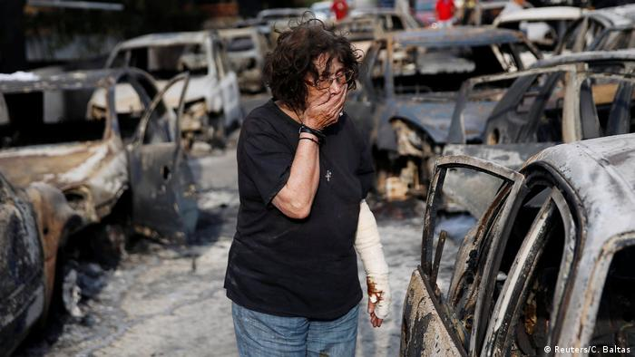 A woman reacts as she tries to find her dog, following a wildfire at the village of Mati