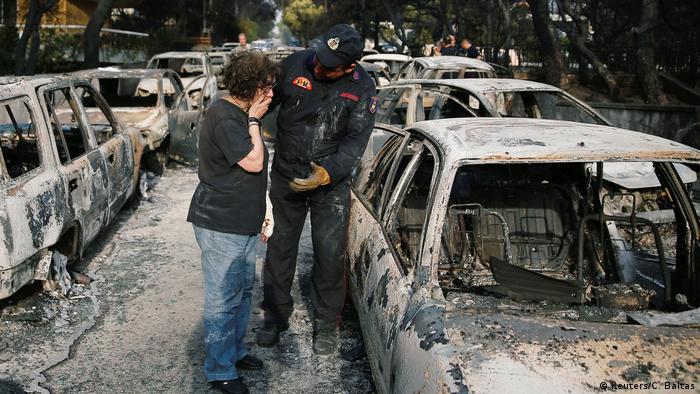 Bombeiro tenta consolar mulher que procura seu cachorro em meio a carros destruídos em Mati