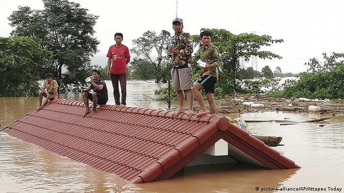 Селяни рятуються на даху будинку після прориву дамби в Лаосі