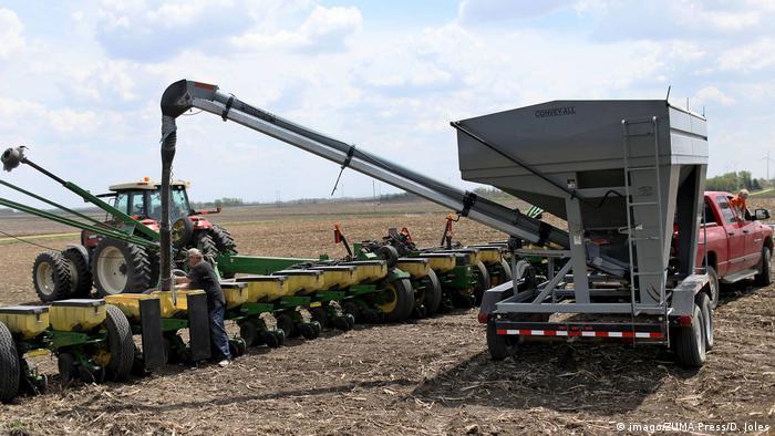 Farmers in Lake Benton, Minnesota load soya beans into a planter on a family farm