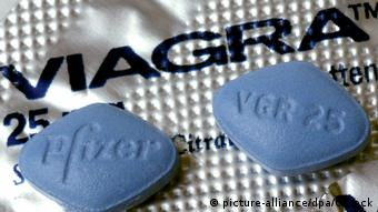 Two blue Viagra pills lie on a packet with the words 'Viagra'