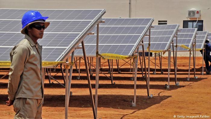 Ein Arbeiter steht vor Solaranlagen