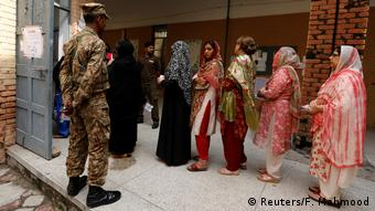 A soldier watches on as women line up at a polling station in Rawalpindi, Pakistan (Reuters/F. Mahmood)