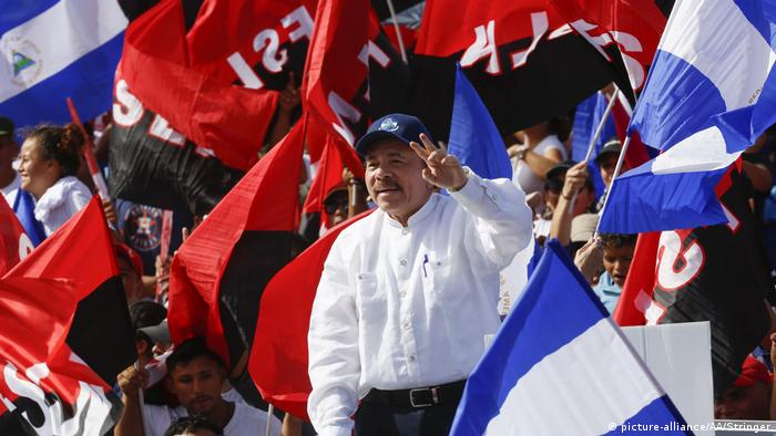 Daniel Ortega raises his hand as flags wave around him (picture-alliance/AA/Stringer)