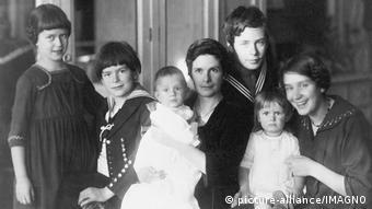 Fotografia antiga em preto e branco mostra mulher com seis filhos