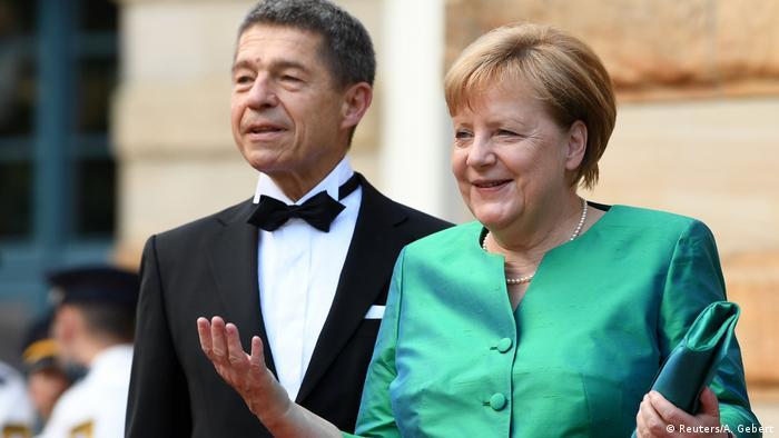 Homem com traje de gala e mulher de roupa verde e carteira da mesma cor