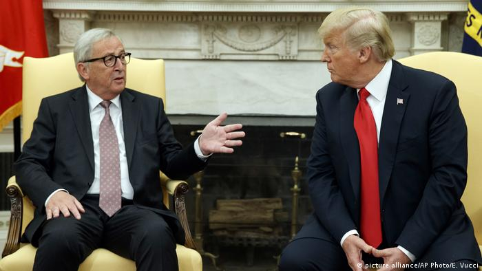 Juncker gestures to Trump as both chat with one another in chairs