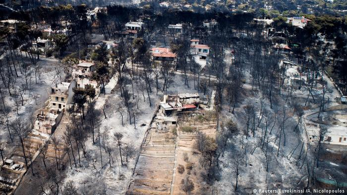 An aerial view shows burnt houses and trees following a wildfire in the Greek town of Mati.