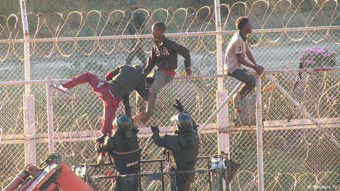 5ef2b85c2e Jovens migrantes escalam cerca de arame farpado em Ceuta