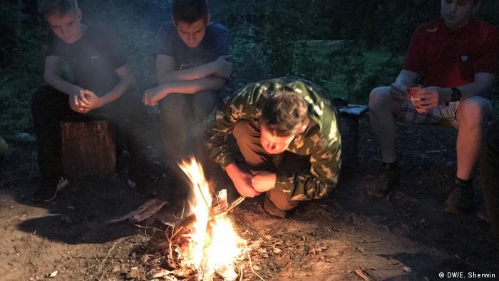 După o zi lungă și obositoare, participanții stau de vorbă în jurul focului de tabără (DW/E. Sherwin)