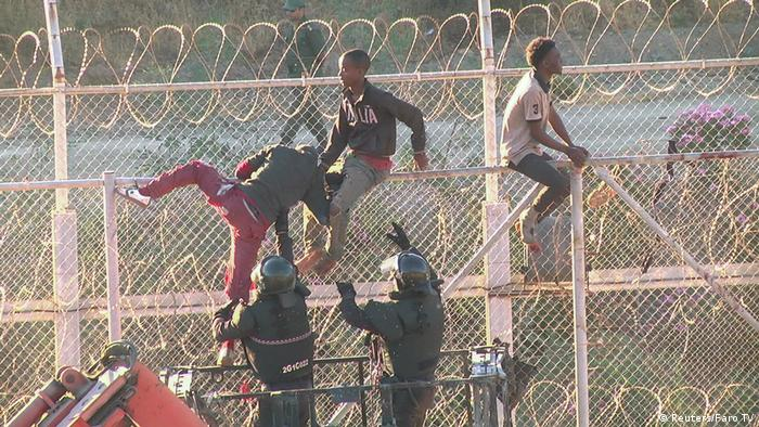 African migrants seen climbing the border between Morocco and Spain's North African enclave of Ceuta