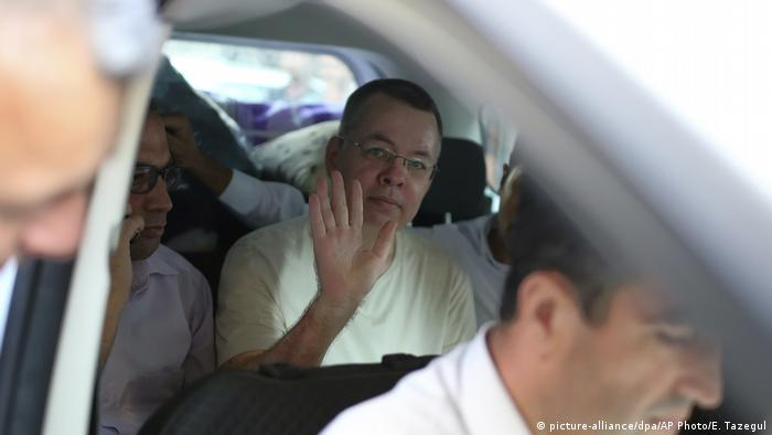 Andrew Brunson waves from a car as he is transferred from prison to house arrest
