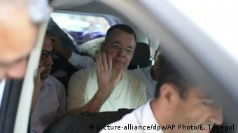 Andrew Brunson waves from a car as he is transferred to house arrest